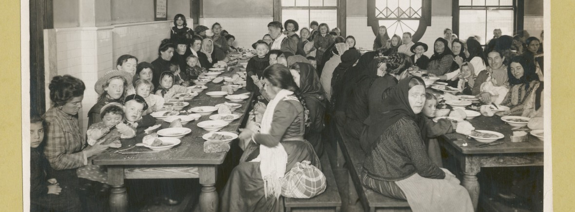 """The Miriam and Ira D. Wallach Division of Art, Prints and Photographs: Photography Collection, The New York Public Library. """"Uncle Sam, host. Immigrants being served a free meal at Ellis Island."""" The New York Public Library Digital Collections. 1902 - 1913. http://digitalcollections.nypl.org/items/510d47da-d817-a3d9-e040-e00a18064a99"""
